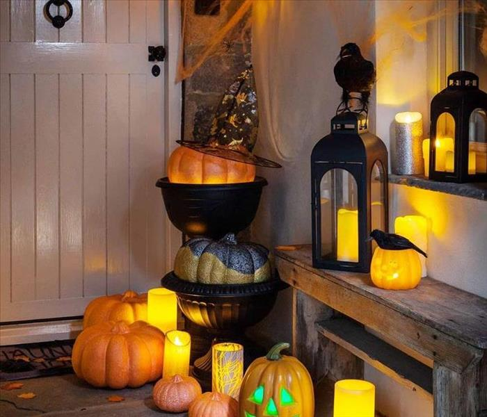 A Halloween display set up on a front porch consisting of battery-operated candles, pumpkins, leaves, cauldrons, and a crow.